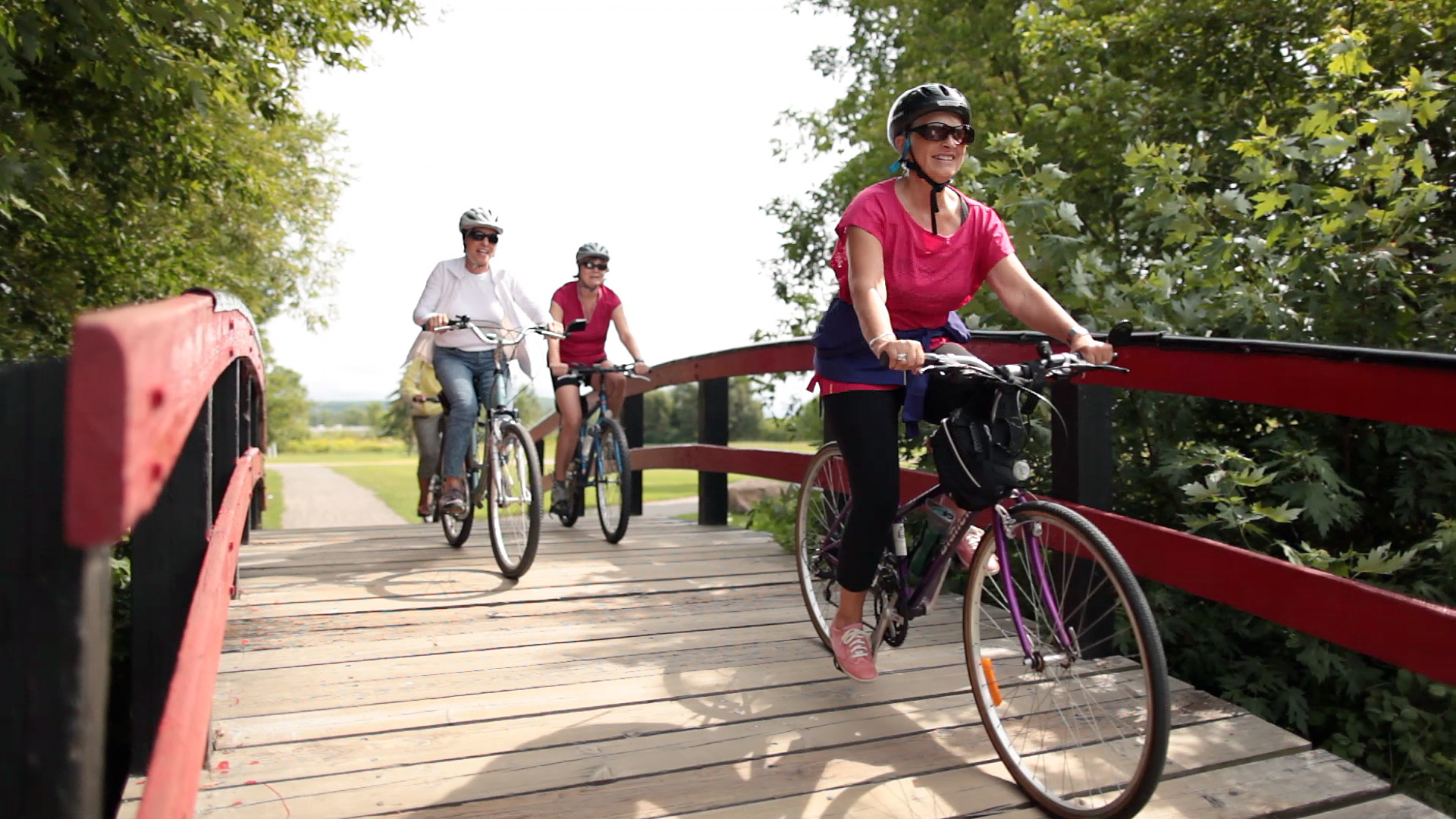 A photo of three ladies biking over a bridge
