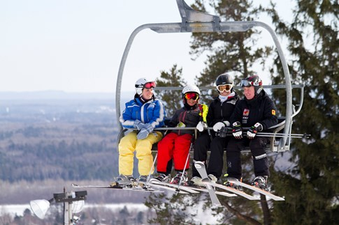 A photo of four skiers on a chair lift